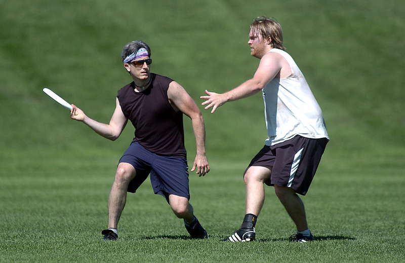 "Scott Potter, left, Sleeveless"", looks for an open player past Tim Matthews, Blue"" during the Grass Roots Ultimate Frisbee tournament at Broomfield County Commons Park on Saturday.<br /> August 21, 2010<br /> staff photo/David R. Jennings"