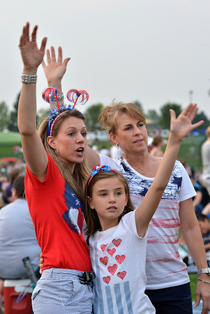 Heather Rider, left, raises her hands with her daughter Aria, 8, and mother Joanne Seaman while listening to the music of Soul School during Broomfield's Great American Picnic at the Broomfield County Commons Park on Wednesday.<br /> <br /> JJuly 4, 2012<br /> staff photo/ David R. Jennings