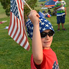 xxx at Sam Cardona, 7, carries a flag while walking with the Bike Parade at Broomfield's Great American Picnic on Wednesday.<br /> <br /> JJuly 4, 2012<br /> staff photo/ David R. Jennings
