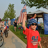 Sam Cardona, 7, holds up a flag while walking in the Bike Parade during Broomfield's Great American Picnic at the Broomfield County Commons Park on Wednesday.<br /> <br /> JJuly 4, 2012<br /> staff photo/ David R. Jennings