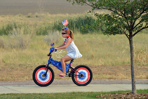 "Leah Abeyta, 8, rides her bicycle in the Bike Parade at Broomfield's Great American Picnic at Community Park on Wednesday.<br /> <br /> July 4, 2012<br /> staff photo/ David R. Jennings<br /> <br /> More photos and video please go to <br />  <a href=""http://www.broomfieldenterprise.com"">http://www.broomfieldenterprise.com</a>"