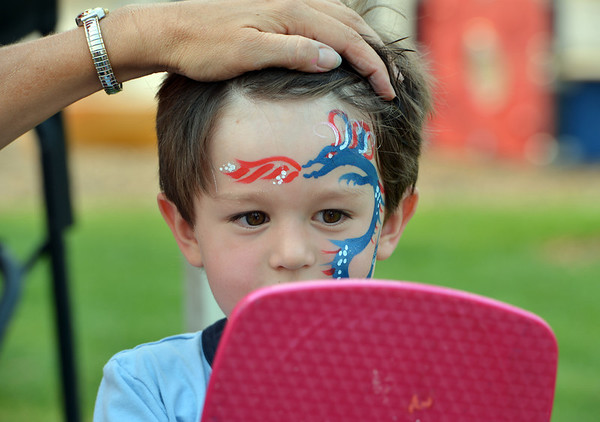 Noah Pollock, 3, looks at the dragon painted on his face during Broomfield's Great American Picnic at the Broomfield County Commons Park on Wednesday.<br /> <br /> JJuly 4, 2012<br /> staff photo/ David R. Jennings