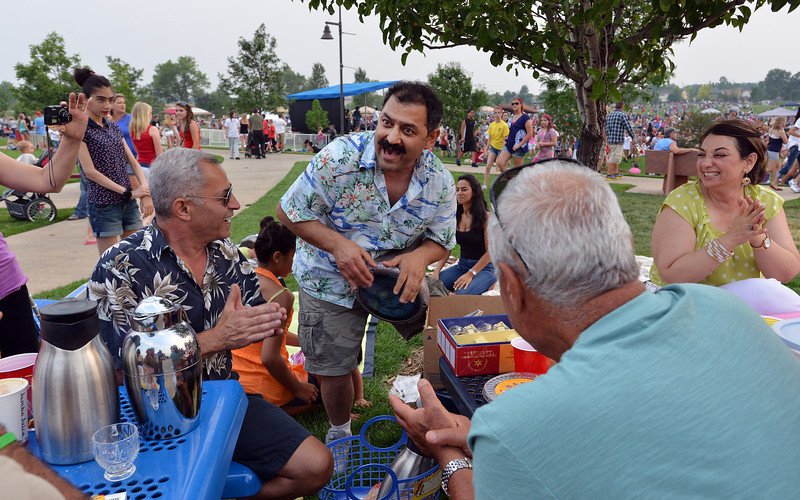 Abbas Asker, left, listens to Bagher Whaddi play a traditional Iranian drum while singing with his family Broomfield's Great American Picnic at the Broomfield County Commons Park on Wednesday. Whaddi just came from Iran to live in the United States and is celebrating his first Fourth of July.<br /> <br /> JJuly 4, 2012<br /> staff photo/ David R. Jennings