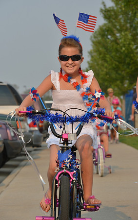 Leah Abeyta, 8, rides her bicycle in the Bike Parade at Broomfield's Great American Picnic at Community Park on Wednesday.<br /> <br /> JJuly 4, 2012<br /> staff photo/ David R. Jennings