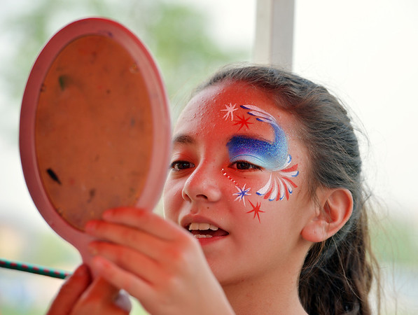 Savanah Bustamante, 11, looks at her painted face during Broomfield's Great American Picnic at the Broomfield County Commons Park on Wednesday.<br /> <br /> JJuly 4, 2012<br /> staff photo/ David R. Jennings