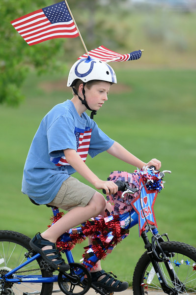 Devin Swift, 11, rides his bicycle during the bike parade at Broomfield's Great American Picnic at Broomfield County Commons on Sunday.  The fireworks show was canceled due to the severe weather.<br /> <br /> <br /> July 4, 2010<br /> Staff photo/ David R. Jennings