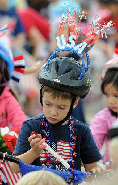 Kieran Brillhart, 4 1/2, looks at a flashlight before the bike parade at Broomfield's Great American Picnic at Broomfield County Commons on Sunday.  The fireworks show was canceled due to the severe weather.<br /> <br /> <br /> July 4, 2010<br /> Staff photo/ David R. Jennings