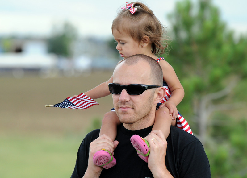 Kevin Hulquest carries his daughter Sophia, 1 1/2, as she waves the flag during the bike parade at Broomfield's Great American Picnic at Broomfield County Commons on Sunday.  The fireworks show was canceled due to the severe weather.<br /> <br /> <br /> July 4, 2010<br /> Staff photo/ David R. Jennings