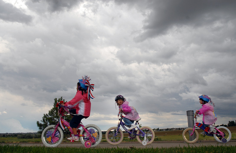 Marissa Martinez,4, left, rides with friends Isabel Pych, 6, and Sophia Pych, 4, as storm cloud loom over the bike parade at Broomfield's Great American Picnic at Broomfield County Commons on Sunday.  The fireworks show was canceled due to the severe weather.<br /> <br /> <br /> July 4, 2010<br /> Staff photo/ David R. Jennings