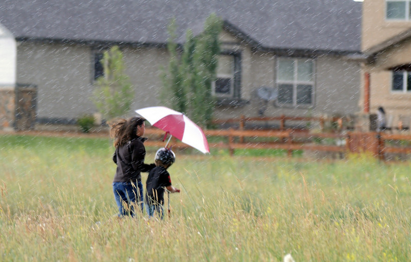Great American Picnic participants head back to the Red Leaf neighborhood in the rain at Broomfield County Commons on Sunday.  The fireworks show was canceled due to the severe weather.<br /> <br /> <br /> July 4, 2010<br /> Staff photo/ David R. Jennings