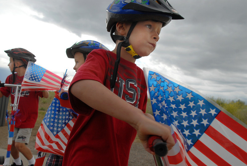 Ryan Hambleton, 5, right, with his twin Bradley, and older brother Dillon, 8, prepare to ride their decorated scooters in the bike parade at Broomfield's Great American Picnic at Broomfield County Commons on Sunday.  The fireworks show was canceled due to the severe weather.<br /> <br /> <br /> July 4, 2010<br /> Staff photo/ David R. Jennings
