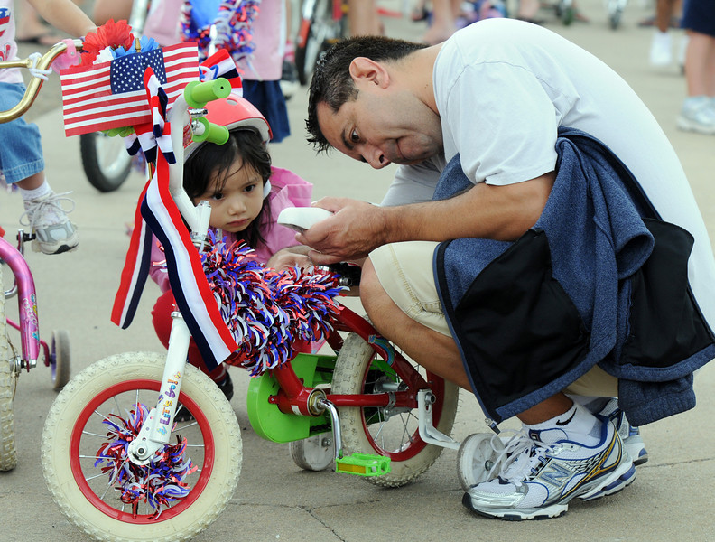 Marissa Martinez, 4, watches her father Tony make adjustments to her bicycle before  the bike parade at Broomfield's Great American Picnic at Broomfield County Commons on Sunday.  The fireworks show was canceled due to the severe weather.<br /> <br /> <br /> July 4, 2010<br /> Staff photo/ David R. Jennings