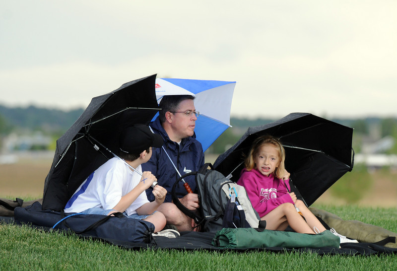 Anthony DeCosmo, center, tries to wait out the storm with his children Tony, 13, left, and Elizabeth, 9, at Broomfield's Great American Picnic at Broomfield County Commons on Sunday.  Later in the evening the fireworks show was canceled due to the severe weather.<br /> <br /> <br /> July 4, 2010<br /> Staff photo/ David R. Jennings
