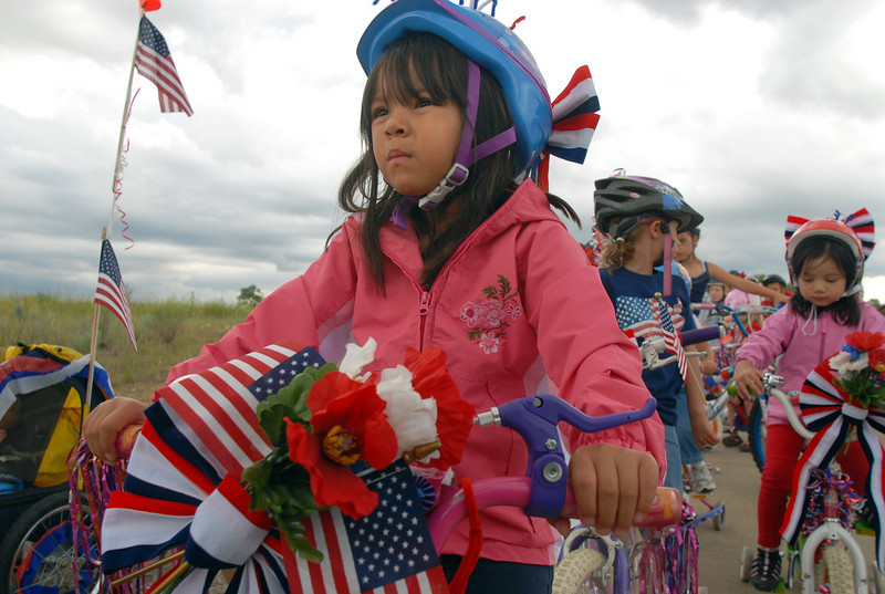 Isabella Martinez, 6, rides in the bike parade at Broomfield's Great American Picnic at Broomfield County Commons on Sunday.  The fireworks show was canceled due to the severe weather.<br /> <br /> <br /> July 4, 2010<br /> Staff photo/ David R. Jennings