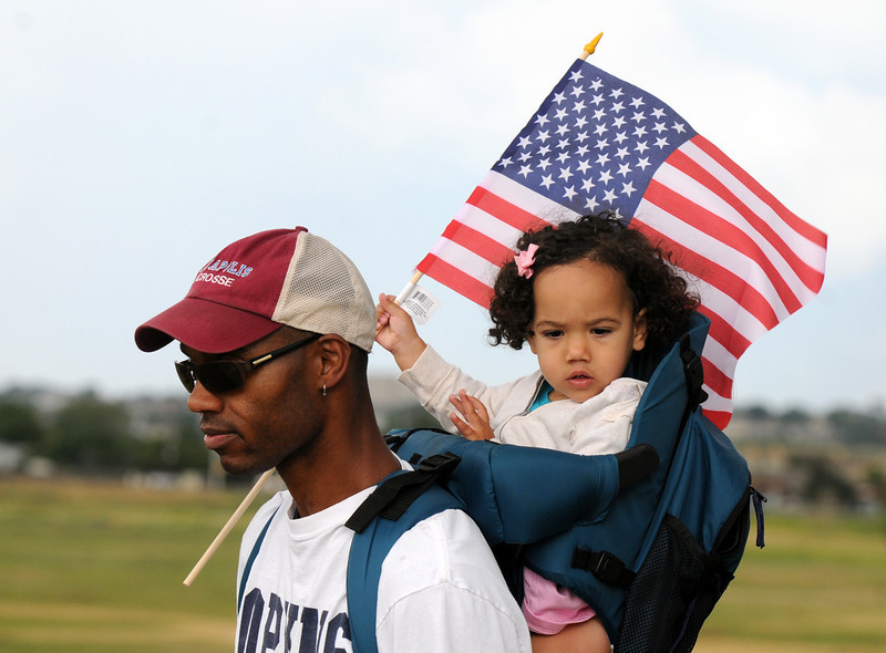 Dax Roane carries his daughter Lucy, 1 1/2, as she waves the flag during the bike parade at Broomfield's Great American Picnic at Broomfield County Commons on Sunday.  The fireworks show was canceled due to the severe weather.<br /> <br /> <br /> July 4, 2010<br /> Staff photo/ David R. Jennings