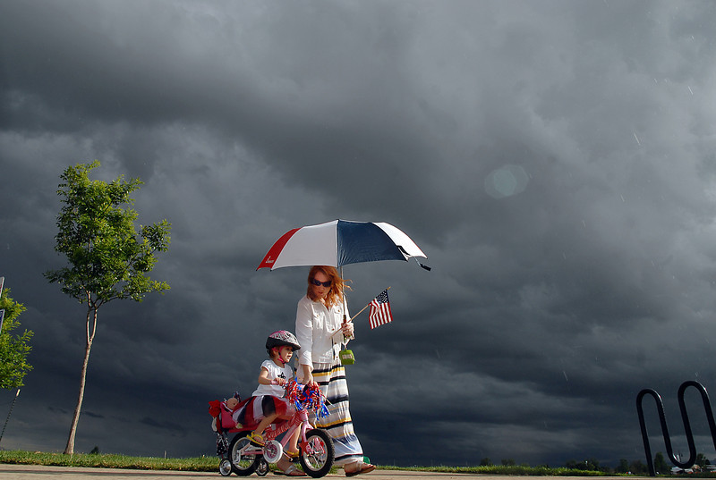 Madelynn Rarimi, 3, with her mother, Heather, rides in the bike parade  as storm clouds form behind at Broomfield's Great American Picnic at Broomfield County Commons on Sunday.  The fireworks show was canceled due to the severe weather.<br /> <br /> <br /> July 4, 2010<br /> Staff photo/ David R. Jennings