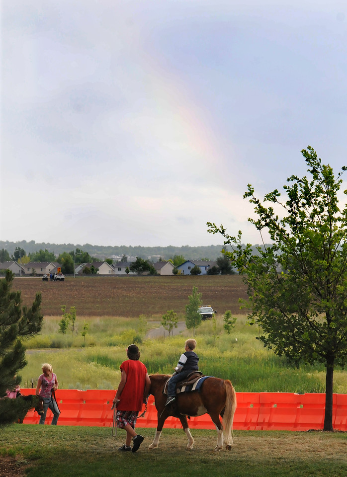 A faint rainbow shows over the pony rides during the Great American Picnic at Broomfield County Commons on Sunday.  The fireworks show was canceled due to the severe weather.<br /> <br /> <br /> July 4, 2010<br /> Staff photo/ David R. Jennings