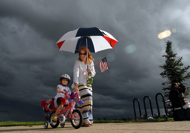 Madelynn Rarimi, 3, with her mother, Heather, rides in the bike parade  as storm clouds form behind at Broomfield's Great American Picnic at Broomfield County Commons on Sunday. <br /> <br /> <br /> July 4, 2010<br /> Staff photo/ David R. Jennings