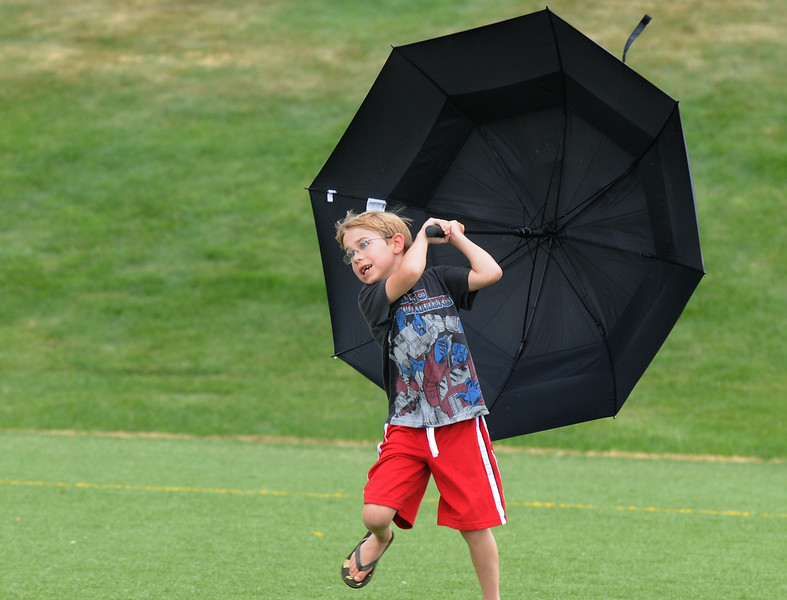 Luke Thiret, 7, plays with an umbrella in the wind at Broomfield's Great American Picnic at Broomfield County Commons on Sunday.  The fireworks show was canceled due to the severe weather.<br /> <br /> <br /> July 4, 2010<br /> Staff photo/ David R. Jennings