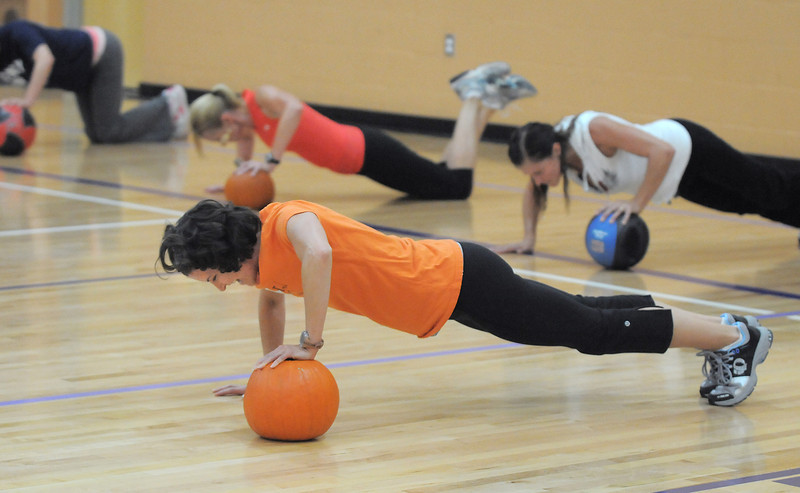 Dawn Keating uses a pumpkin as an aid for push-ups during the Great Pumpkin Workout on Wednesday at the Derda Recreation Center.<br /> October 26, 2011<br /> staff photo/ David R. Jennings