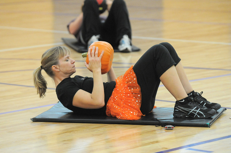Katie Richards works on her abs using a pumpkinduring the Great Pumpkin Workout on Wednesday at the Derda Recreation Center.<br /> October 26, 2011<br /> staff photo/ David R. Jennings