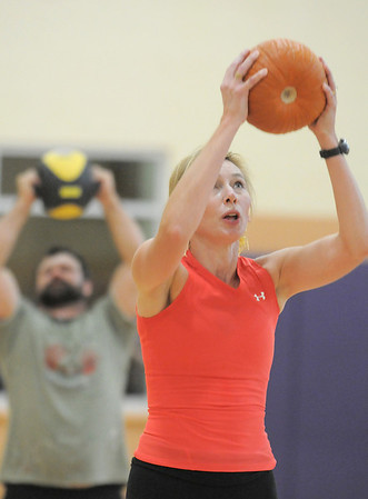 Karen Hopley holds a pumpkin over her head with Brian Norcross working with a workout ball while exercising during the Great Pumpkin Workout on Wednesday at the Derda Recreation Center.<br /> October 26, 2011<br /> staff photo/ David R. Jennings