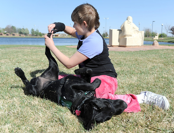Anna Nicodemus, 11, touches Bonita's feet to help the puppy get used to human interactions during a Guide Dogs for the Blind, puppy in training demonstration at Community Park.<br /> April 6, 2012 <br /> staff photo/ David R. Jennings