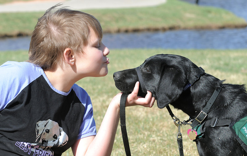 Anna Nicodemus, 11, blows a kiss to Bonita, a black lab, during a break in the Guide Dogs for the Blind, puppy in training demonstration at Community Park.<br /> <br /> April 6, 2012 <br /> staff photo/ David R. Jennings