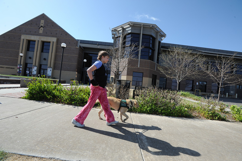 Anna Nicodemus, 11, walks with Keena past the Mamie Doud Eisenhower Public Library heading to a Guide Dogs for the Blind, puppy in training demonstration at Community Park.<br /> April 6, 2012 <br /> staff photo/ David R. Jennings