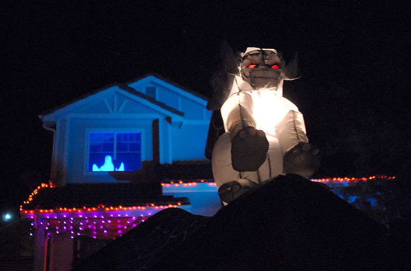 A lighted gargoyle at night with a ghost in the window of the house at the 14341 Craftsman Way Halloween display on Thursday<br /> <br /> October 21, 2010<br /> staff photo/David R. Jennings