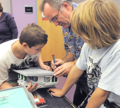 Larry Price, center, with Jacob Averhoof, 13, left, and his brother Nathan, 10, work on a wire for a model for the Hands-On Model Railroads exhibit by Youth in Model Railroading on Saturday at the Mamie Doud Eisenhower Public LIbrary. <br /> October 8, 2011<br /> staff photo/ David R. Jennings