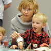 Iva Roba with her son Michael, 4 1/2, right, and daughter Sofie 19 months-old, study which objects move and light up when they press a button on the control panel during the Hands-On Model Railroads exhibit by Youth in Model Railroading on Saturday at the Mamie Doud Eisenhower Public LIbrary. <br /> October 8, 2011<br /> staff photo/ David R. Jennings