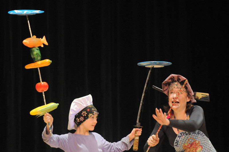 Cindy Marvell, right, spins plates using an audience member during the Lazer Vaudeville performance at the Happy Noon Year celebration on Friday at the Broomfield Auditorium.<br /> December 31, 2010<br /> staff photo/David R. Jennings