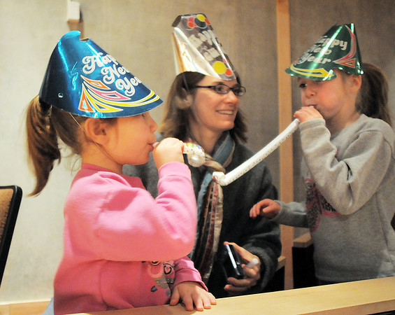 Cecilia Guerrera, 4, left, blows her noise maker with her mother Rachel and sister Teresa, 5, at the Happy Noon Year celebration after the performance by Lazer Vaudeville on Friday at the Broomfield Auditorium.<br /> December 31, 2010<br /> staff photo/David R. Jennings