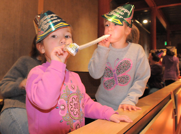 Cecilia Guerrera, 4, left, blows her noise maker with her Teresa, 5, at the Happy Noon Year celebration after the performance by Lazer Vaudeville on Friday at the Broomfield Auditorium.<br /> December 31, 2010<br /> staff photo/David R. Jennings