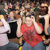 Anthony Bowles, 11, center, is hit by noise makers blown by his sister Melita, 8, left, and brother Balor, 10, at the Happy Noon Year celebration after the performance by Lazer Vaudeville on Friday at the Broomfield Auditorium.<br /> December 31, 2010<br /> staff photo/David R. Jennings