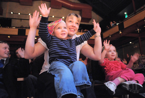 "Amy Tabor and her son Cody, 3, with Kinley Hollonds, 3, right, raise their arms into the air while following the directions of clown Jim Jackson during his performance at the Happy Noon Year celebration at the Broomfield Auditorium on Saturday. <br /> <br /> More photos please see  <a href=""http://www.broomfieldenterprise.com"">http://www.broomfieldenterprise.com</a><br /> December 31, 2011<br /> staff photo/ David R. Jennings"
