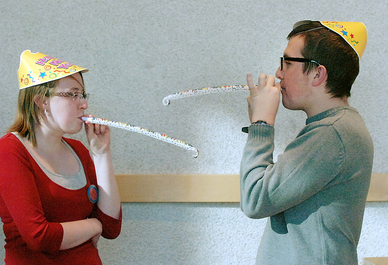 Library volunteers Kelsey Kalmbach, 18, left, and her brother Sawyer, 16, blow their noisemakers in the lobby of the Broomfield Auditorium after the Happy Noon Year celebration on Saturday. <br /> <br /> December 31, 2011<br /> staff photo/ David R. Jennings