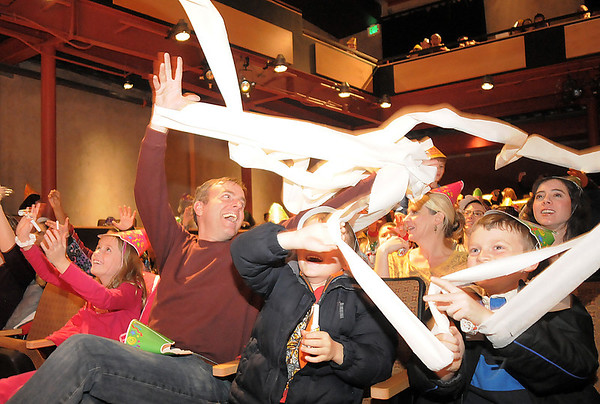 "Mark Wakefield, second left, with his children Rachel, 8, left, Micah, 6, and Caleb, 8, cheer as toiler paper confetti rains down on the audience during the Happy Noon Year celebration at the Broomfield Auditorium on Saturday. <br /> <br /> More photos please see  <a href=""http://www.broomfieldenterprise.com"">http://www.broomfieldenterprise.com</a><br /> December 31, 2011<br /> staff photo/ David R. Jennings"