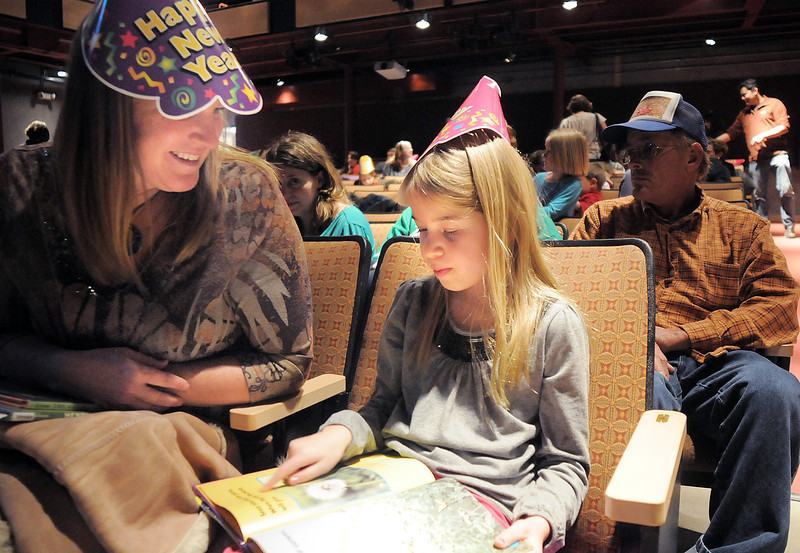 """C.C. Smith, 7, right, reads the book """" It's Windy Today"""" to her mother Charlene while waiting for the Happy Noon Year celebration to begin at the Broomfield Auditorium on Saturday. <br /> <br /> December 31, 2011<br /> staff photo/ David R. Jennings"""
