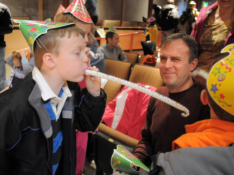 Caleb Wakefield, 8, left, blows a noisemaker at his brother Micah, 6, and their father Mark, center, after the Happy Noon Year celebration at the Broomfield Auditorium on Saturday. <br /> <br /> December 31, 2011<br /> staff photo/ David R. Jennings