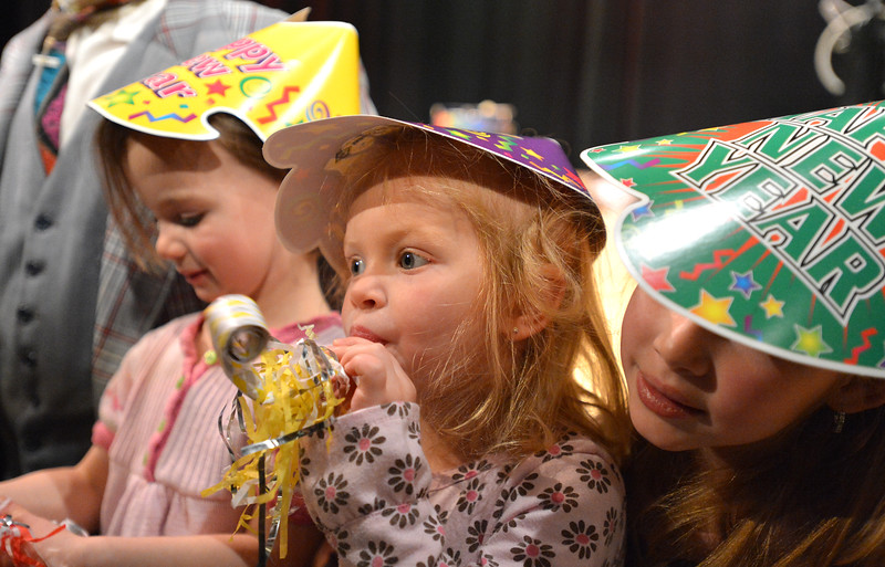 Mia Kidd, 3, center, blows her noise maker with Clare Martin, 4, left, and Siena Kidd, 5, during the Happy Noon Year celebration with a sold out crowd at the Audi on Monday.<br /> December 31, 2012<br /> staff photo/ David R. Jennings