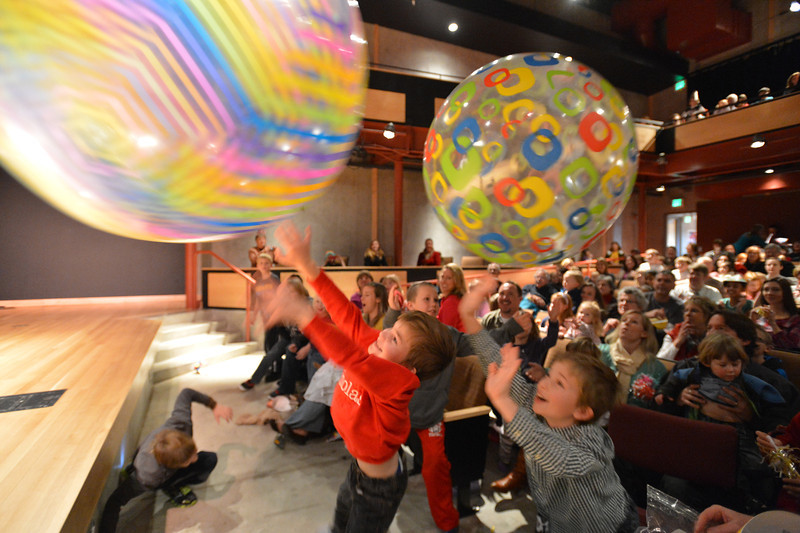 Nicholas Kastner, 6, left, and his brother Michael Lee, 8, hit giant beach balls back to performer Peter Davison during the Happy Noon Year celebration at the Audi on Monday.<br /> December 31, 2012<br /> staff photo/ David R. Jennings