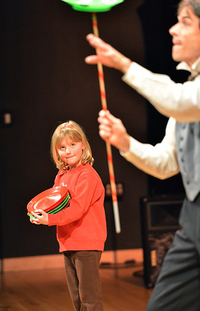 Hannah Christianson, 5, watches Peter Davison balance spinning plastic plates during his performance at the Happy Noon Year celebration at the Audi on Monday.<br /> December 31, 2012<br /> staff photo/ David R. Jennings