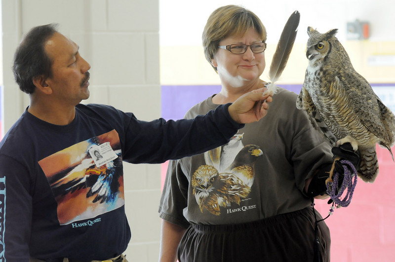 Master falconer Kin Quitugua, left, uses a feather to point out the ears on a Great Horned Owl, held by volunteer Lynn Logman, are just feathers during a presentation by HawkQuest to Westlake Middle School 6th graders in the Wolf Pack Corps on Tuesday.<br /> <br /> November 24, 2009<br /> Staff photo/David R. Jennings