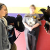 Taylor Makowski, left, gets a prey's perspective as a Harris Hawk flies to the gloved arm of HawkQuest master falconer Kin Quitugua during his presentation to Westlake Middle School 6th graders in the Wolf Pack Corps on Tuesday.<br /> <br /> November 24, 2009<br /> Staff photo/David R. Jennings