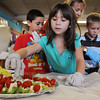 Sabrina Atencio, front, helps make a tray of celery, cream cheese and tomato snacks with Alex Najera, left, and Mike Gross and teacher Miki Novaria during Emerald Elementary School 2nd grader's  Healthy Learning Paths program by Dr. Chris Marchioni on Tuesday.<br /> <br /> October 20, 2009<br /> Staff photo/David R. Jennings