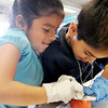Emerald Elementary School 2nd graders Marlen Guitierrez, left, and Marco Coronado Barrios slice an apple while preparing healthy snacks for the Healthy Learning Paths program by Dr. Chris Marchioni on Tuesday.<br /> <br /> October 20, 2009<br /> Staff photo/David R. Jennings