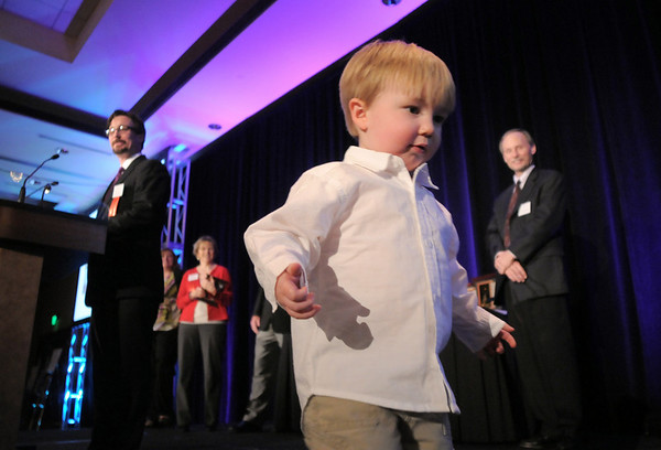 River Conly, 2, plays on the stage while his father, Brian, gives his acceptance speech fo rthe Education Award during the Broomfield Community Foundation's Heart of Broomfield awards ceremony at the Omni Interlocken Resort Hotel on Monday..<br /> <br /> April 18, 2011<br /> staff photo/David R. Jennings
