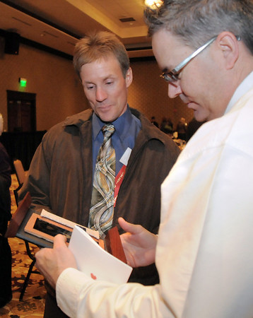 John Mooney, right, looks at the Community Service Award given to Mike Lutz  at the Broomfield Community Foundation's Heart of Broomfield awards ceremony at the Omni Interlocken Resort Hotel on Monday.<br /> <br /> April 18, 2011<br /> staff photo/David R. Jennings